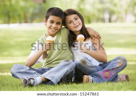 Two children eating ice cream in park looking to camera