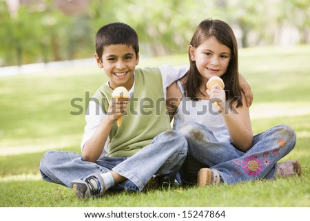 Two children eating ice cream in park looking to camera - stock photo