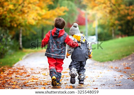 Two children, fighting over toy in the park on a rainy day, autumn time #325548059