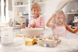 Two children having fun baking in the kitchen