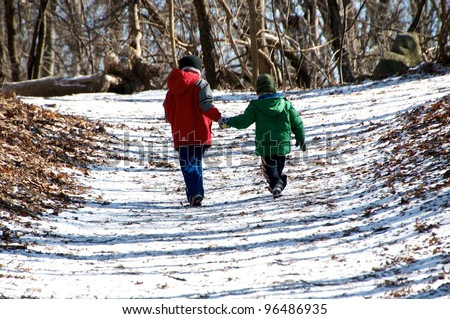 Two children hold hands and run down the path