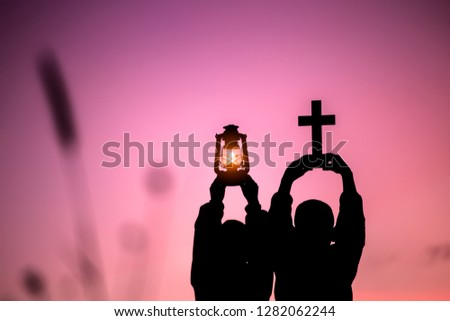 Two children holding oil lamp and cross with light sunset background,christian concept.