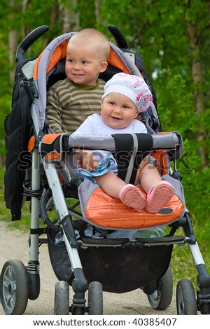 Two children in baby carriage. There is one year's difference of age between them. They are brother and sister - stock photo