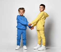 Two children in stylish bright sports suits sitting holding hands on a white background. Cute little boy and girl posing in the studio showcasing a new collection of sportswear for children.