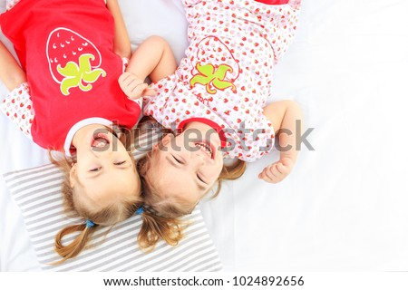 Two children lie in a pajamas bed. The concept of childhood, lifestyle, morning. Copy space. The concept of childhood, lifestyle, game. #1024892656