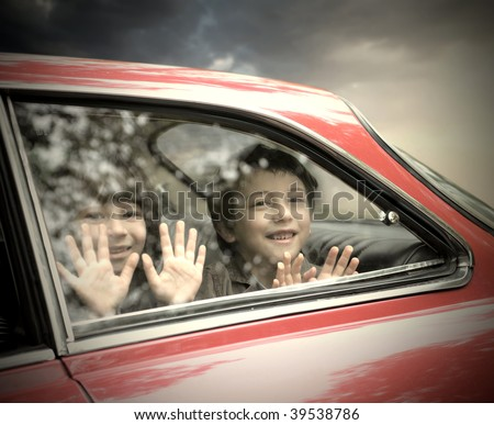 two children looking trough car window