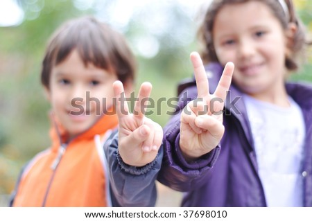 Two children, male and female with victory fingers