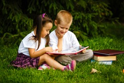Two children of younger school age, the boy and the girl are reading books on the green grass. Back to school. Young student doing homework. Education for small kids.