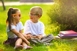 Two children of younger school age, the boy and the girl are reading books on the green grass. Warm spring day. School students have an excellent mood.