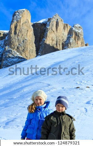 Two children on beautiful winter mountain slope (Sella Pass , Italy).