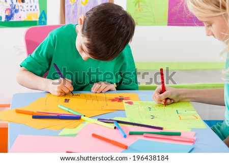 Two children paint markers on the colored paper