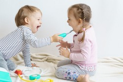 Two children play doctor in the nursery. Brother in yellow glasses treats his sister, playing dentist, ENT, ophthalmologist, temperature measurement. Role-playing games for children