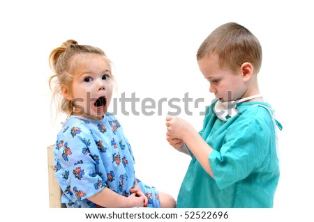 Two children play doctor.  Little girl opens her mouth and says aaah! Panic sets in as the little boy doctor adjusts his instrument.  One is dressed in hospital gown and the other a scrub.