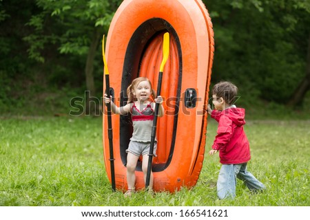 Two children play with paddles and big rubber boat on the nature