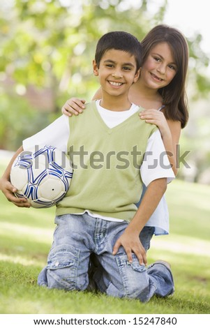Two children playing in park together looking to camera