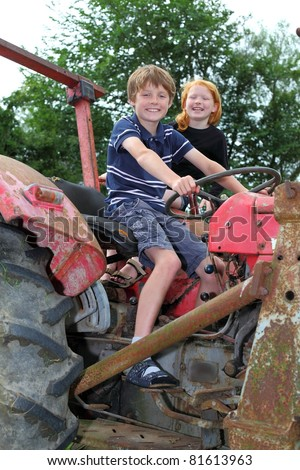 Two children playing on an old tractor - stock photo