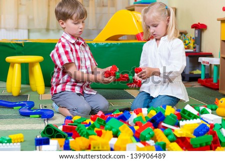 Two children playing with blocks on the floor at home