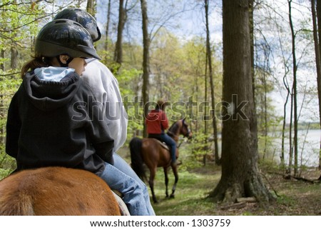 Two children ride double on their horse, with another rider in front of them on the trail.
