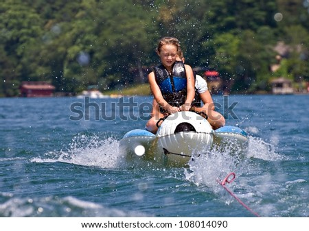 Two children riding a float being splashed by the water.