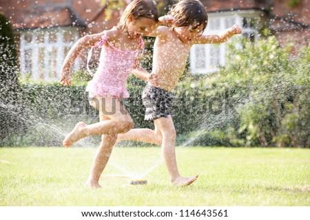 Two Children Running Through Garden Sprinkler ストックフォト ©