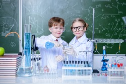 Two children scientists making experiments in the laboratory. Educational concept. Early development of children.