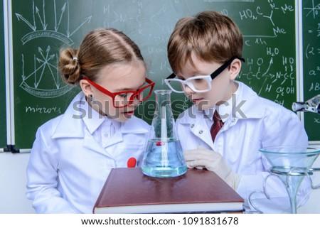 two children scientists making...