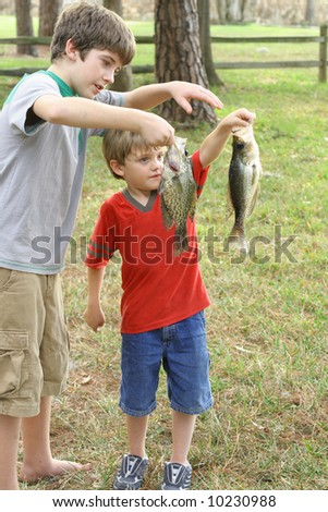 two children showing off their fish - stock photo