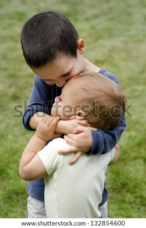 Two children, siblings, small boys, playing together outdoors; the older brother is holding the younger child around his neck, hugging and kissing him.