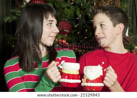 Two children sitting by of a lovely Christmas tree enjoying mugs of hot chocolate.
