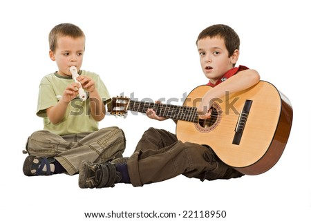 Two children sitting on the floor and playing with musical instruments