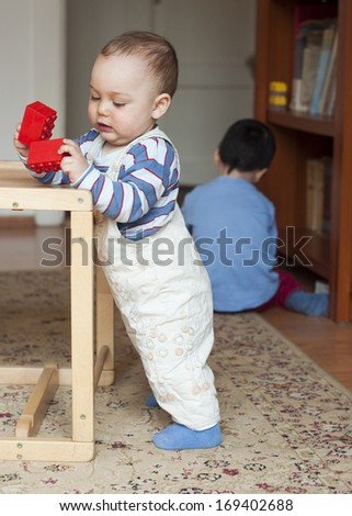 Two children, small toddler or a baby child and his older brother, playing  at home with building blocks.