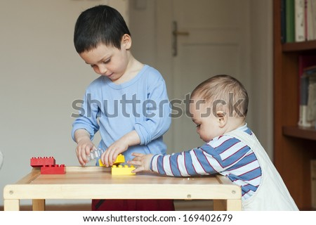 Two children, small toddler or a baby child and his older brother, playing together at home with building blocks on a low table.
