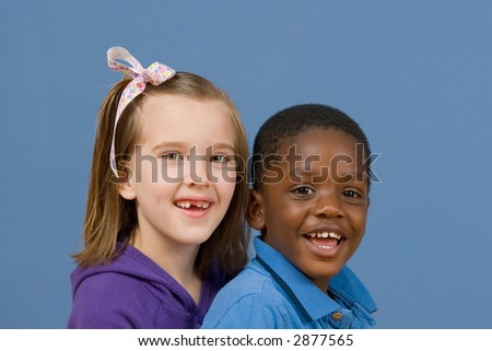 Two children smiling together - an African American boy and a Caucasian girl with a ribbon in her hair.