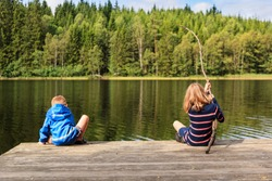 Two children using a homemade fishing rod fishing from a jetty by a lake set in an idyllic Swedish summer forest landscape