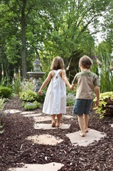 Two children walking down a garden path to a fountain