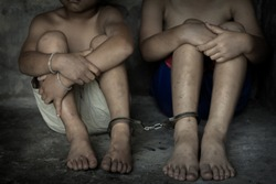 Two children  was a victim of human trafficking, foot tied up with shackle in emotional stress, The concept of stopping violence against children.