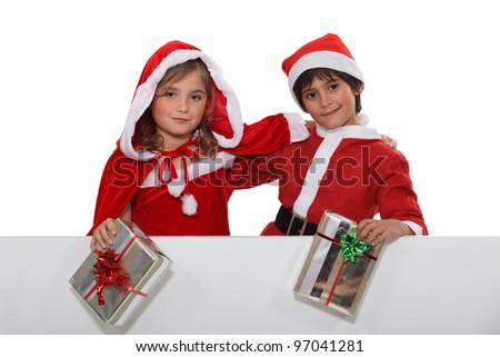 two children wearing Christmas costumes - stock photo