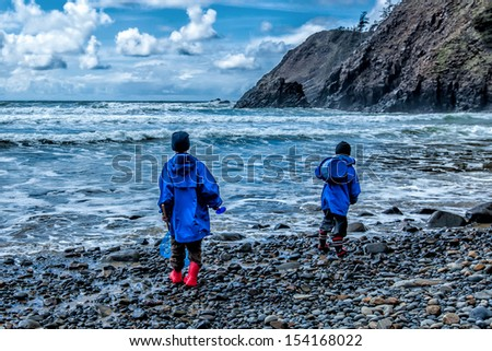 Two children wearing rain jackets and rubber boots play on a rocky beach in stormy weather. Dramatic clouds overhead.