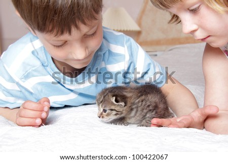 two children with kitten at home
