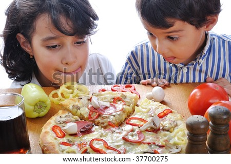 Two children with surprised face on pizza table