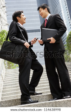 Two Chinese Businessmen Having Discussion Standing Outside Office