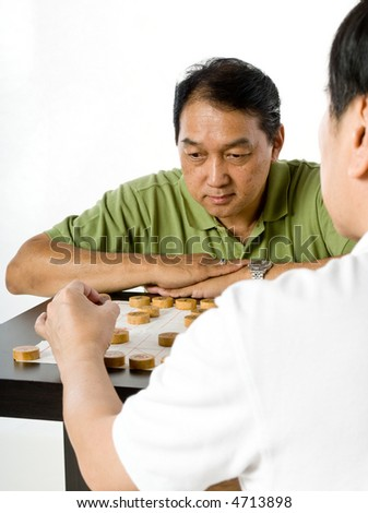 Two Chinese men in their fifties playing chess in the studio