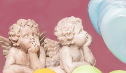 Two chipped cherub statues with chins on hands surrounded by pastel hearts isolated on pink background for Valentine's Day