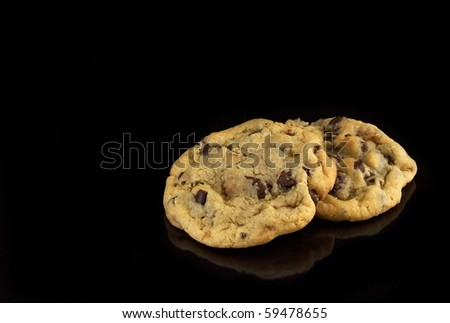 Two Chocolate Chip cookies on black background with copy space