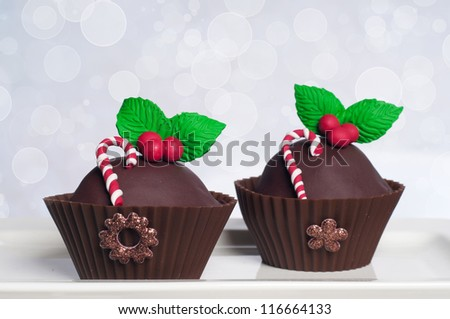 Two chocolate Christmas cupcakes with holly and candy canes on bokeh background
