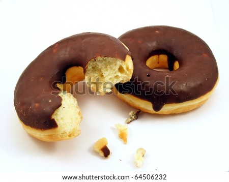 Two chocolate doughnuts, one with a bite taken out & isolated on a white background