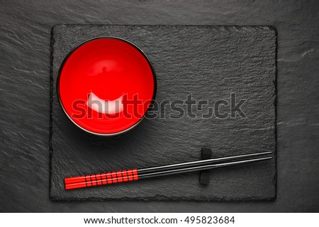 Two chopsticks and red plate on black stone background with copyspace, top view #495823684