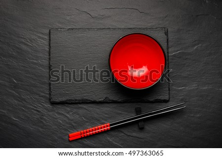 Two chopsticks and red plate on black stone background with copyspace, top view #497363065