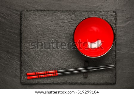 Two chopsticks and red plate on black stone background with copyspace, top view #519299104