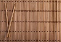 Two chopsticks on sushi mat background for menu